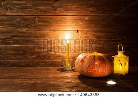 Halloween Carved Pumpkin And Candle On Wooden Background
