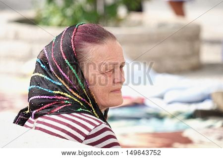OSTROG MONASTERY, MONTENEGRO - JULY 25, 2016: a middle-age woman Christian faith wearing a black veil but brightly colored