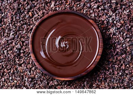 Bowl of melted chocolate on a crushed raw cocoa beans, nibs background. Copy space. Top view