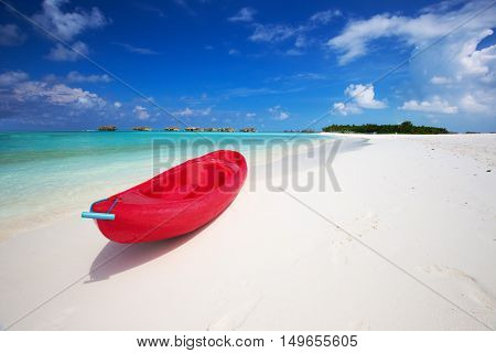 Red kayak on tropic beach with palm trees and overwater bungalows on Maldives island