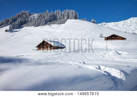 Farmhouse in the Swiss Alps and snow covered mountains near Adelboden