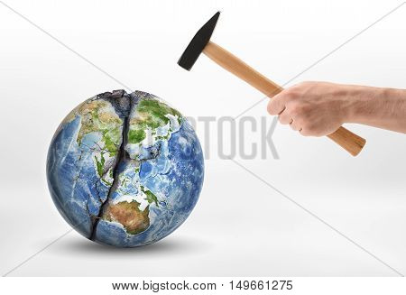 Man's hand with a hammer hits the planet Earth. Anthropogenic impacts. Environmental effects. Harm and damage. Elements of this image are furnished by NASA.