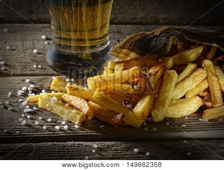 fried french fries and beer on a wooden background