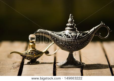 Beautiful antique metal lamp in true Aladin style, smaller model placed next to it, sitting on wooden surface.