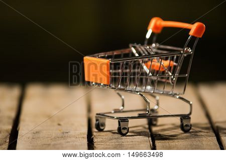 Miniature shopping trolley sitting on wooden surface, magicians concept.