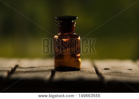 Small brown medicine bottle for magicians remedy sitting on wooden surface, beautiful night light setting, magic concept.