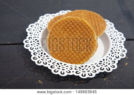 Dutch cookie stroopwafels on white plate on black wooden background