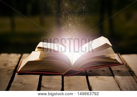 Thick book lying open on wooden surface, magic star dust coming out of it, beautiful night light setting, magician concept shoot.