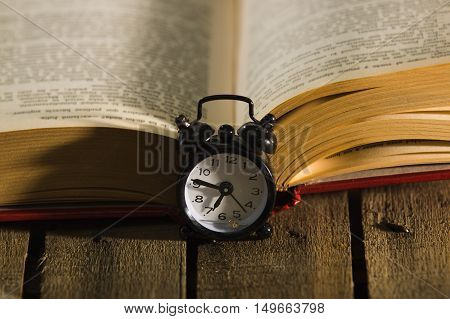 Thick book lying open on wooden surface, old fashioned night table clock sitting next to it, magic concept shoot.