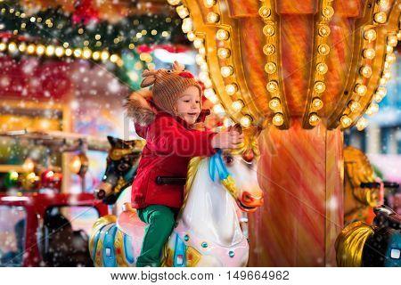 Child Riding Carousel On Christmas Market