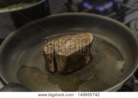 Piece of fillet steak cooking in a pan on a gas hob