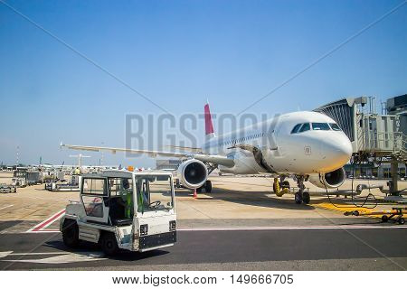 Plane At The Airport During Loading Passengers. Near The Tractor