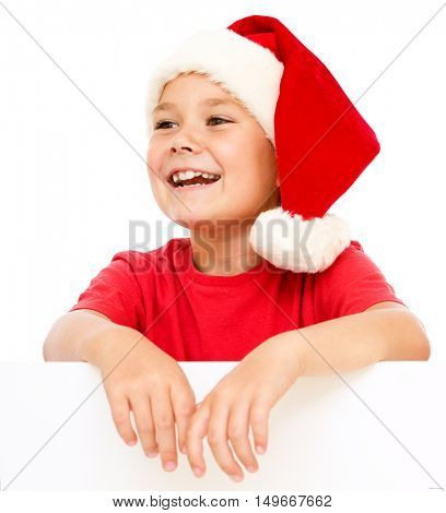 Little girl in santa hat is holding blank board and smiling, isolated over white