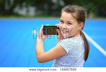 Girl is shooting photo using smartphone, outdoor shoot