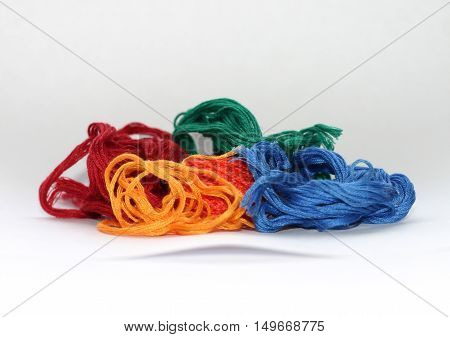 Skeins of tangled colorful sewing threads on the white background