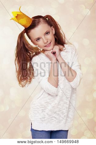 Beautiful cute little princess girl with crown on yellow background