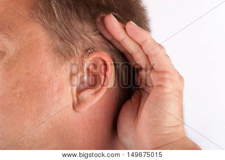 Ear of a man wearing hearing aid and cupping his hand behind his ear.