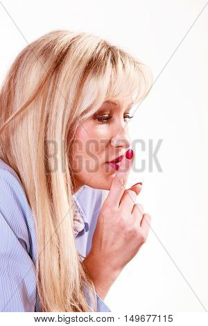 Gesture and communication message.. Mysterious middle age woman with make up holding finger close to lips.