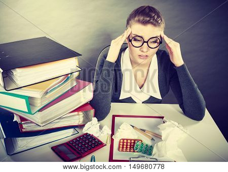 Fatigue and pain concept. Young elegant businesswoman with lot of pills for diseases and aches. Tired sick blonde woman accountant at work.