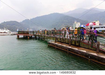 NANTOU TAIWAN - September 04: Tourists walking on a bridge in the main tourist area of Sun moon lake on September 04th 2014 in Nantou
