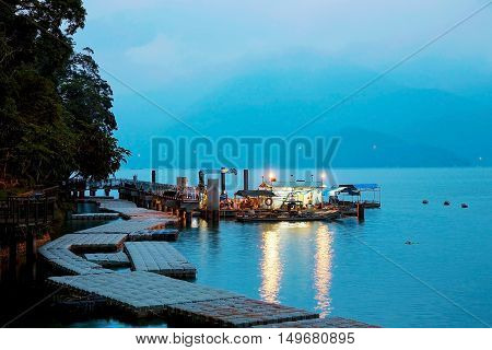 Sun Moon Lake at night time with mountains in the mist