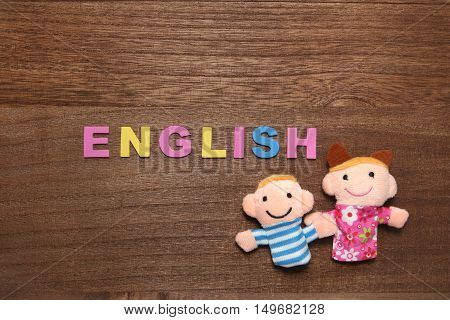 Alphabet letters ENGLISH and children dolls on wood. English education concept.