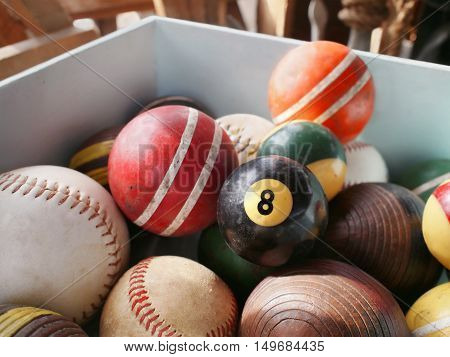 An old eightball in wooden bin full of vintage game balls including pool croquet and baseball.