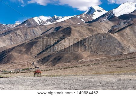 Alone red pavilion alone with snow mountain in background and clear blue sky at Pangong Lake, India.