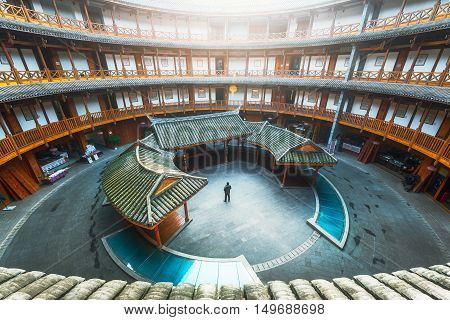 Luodai, Sichuan Province, China - Jan 16, 2016 : Man standing in a Hakka traditional round house with sunlight coming from the roof.