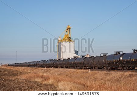 A long train of tank cars passing a prairie grain elevator
