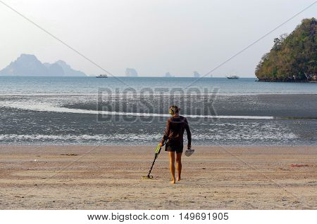 a treasure hunter with Metal detector on sunrise on the beach
