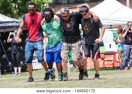 ATLANTA, GA - JULY 2016:  Men move in unison as they take part in a five-legged race one of many kid's games played by adult teams at Atlanta Field Day in the Old Fourth Ward Park in Atlanta GA on July 16 2016.