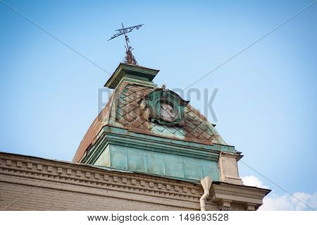 The tower with a weather vane on the roof of an old castle