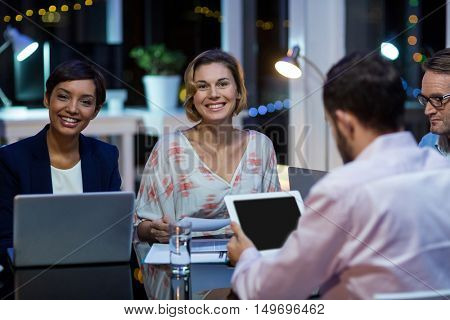 Smiling businesspeople working in office at night