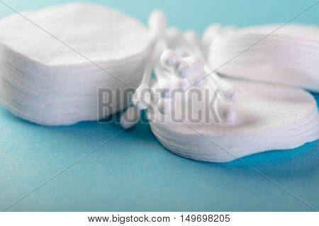 cotton pads and sticks on blue background