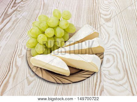 Several slices of Brie cheese and Camembert cheese with cluster of a white table grapes on a dark glass saucer on wooden surface