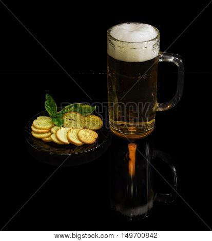 Beer glassware with lager beer rusks with pesto sauce flavor and twig of basil on a saucer on a dark reflective background