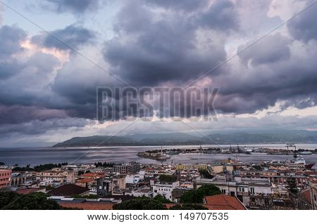 Sunset in the Port of Messina in Sicily Italy. Clouds and sunset light with night illumination.