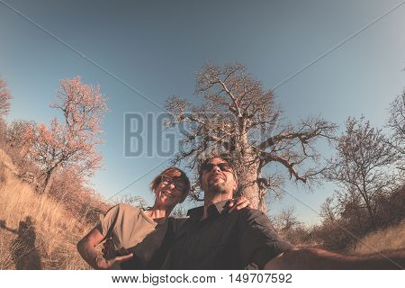 Couple taking selfie near Baobab plant in the african savannah with clear blue sky. Fisheye view from below toned image. Wilderness safari and adventure in Africa.