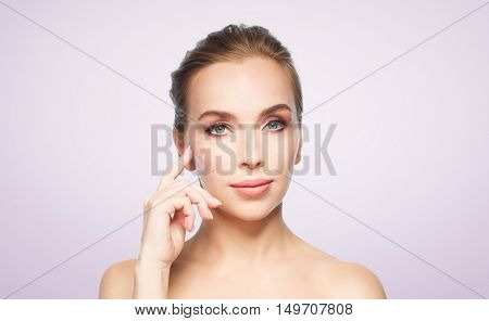 beauty, people and plastic surgery concept - beautiful young woman showing her cheekbone over violet background