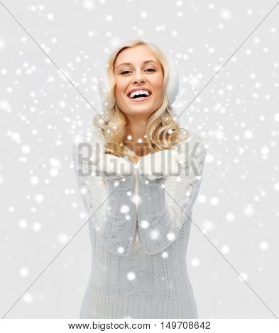 winter, fashion, christmas and people concept - smiling young woman in earmuffs and sweater holding something on her empty palms