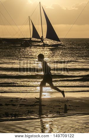 Silhouette of a running boy at amazing orange sunset with boats over the sea at Boracay island Philippines