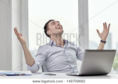 business, people, success and gladness concept - happy businessman with laptop in office