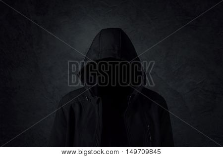 Hooded man silhouette over dark concrete background
