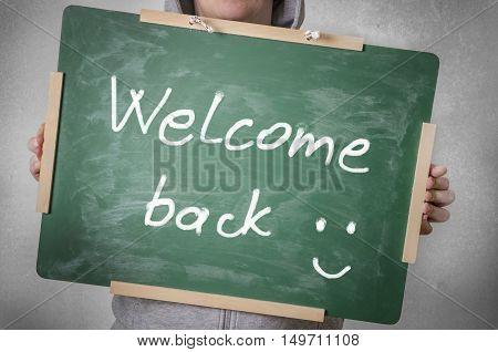 Welcome back written on chalkboard. Back to school concept.