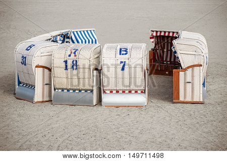 typical Northern German beach chairs called Strandkorb standing in a circle like a dare castle in the sand at the Baltic Sea cheaper holidays in the low season copy space