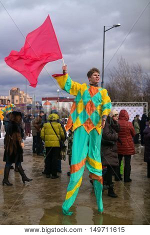 Saint-Petersburg Russia - February 22 2015: Feast Maslenitsa on Vasilyevsky Island. Buffoon with a flag on stilts and calls people to the feast.