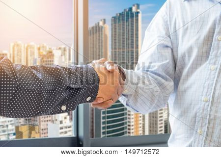 business man and partner handshake with honk kong background