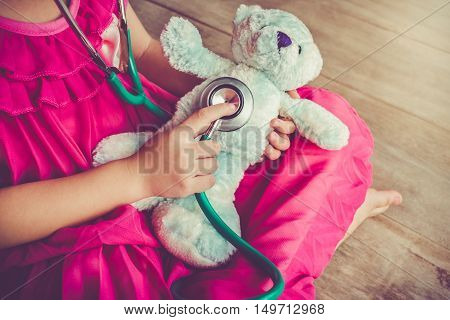 Child playing doctor or nurse with plush toy bear with bright sunlight at home. Happy girl listens a stethoscope to toy. Playful girl role playing. Vintage tone effect.