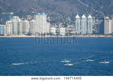 Group of people on a jet skis riding in front of the skyscraper riviera of Acapulco Mexico.